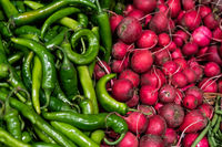 Red radish and hot chili peppers on market. Vegetables background.