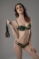 Alluring model in camouflage lingerie holding whip