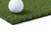 Golf Ball Resting on Section of Artificial Turf Grass On White Background