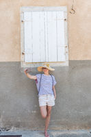 Beautiful young female tourist woman wearing big straw hat, taking self portrait selfie, standing in front of white vinatage wooden window and textured stone wall at old Mediterranean town