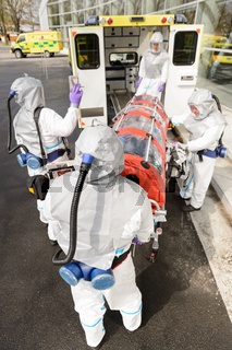 Biohazard team loading stretcher in ambulance