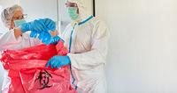Putzkräfte entsorgen infektiösen Müll in Klinik