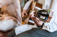 Hand playing classical guitar on sacred music