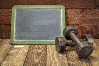blank slate blackboard sign with dumbbells