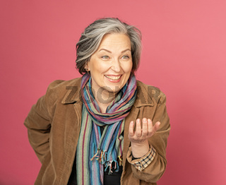 Funny mature woman laughs gesturing by hand and looking at side. Creative aged lady posing in studio on pink background