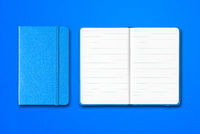 Cyan closed and open lined notebooks isolated on blue background