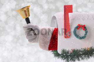 Santa Claus arm holding a Christmas bell coming out of a mail box with silver bokeh background and snow effect.