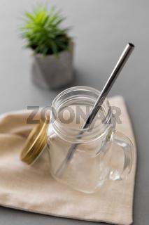 empty glass mug of with reusable metallic straw
