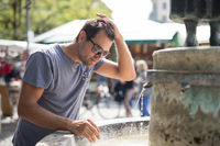Young casual cucasian man refreshing himself with water from public city fountain on a hot summer day