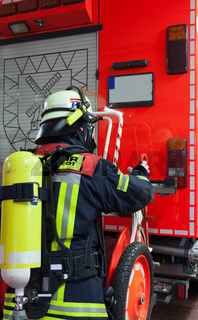 Feuerwehrmann am Einsatzfahrzeug Atemschutzgerät