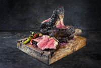 Charred Barbecue dry aged wagyu bistecca alla Fiorentina beef steak offered as close-up on an old rustic wooden board with copy space
