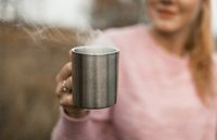Female Hand Holding Cup With Hot Drink Outdoors