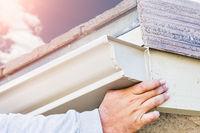 Worker Attaching Aluminum Rain Gutter to Fascia of House