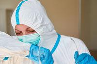 Pflegepersonal in Klinik oder Heim in Schutzkleidung hustet in Armbeuge