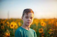 Portrait of beautiful blond kid boy on summer sunflower field