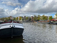Amsterdam canal with typical dutch houses and houseboats, boats etc.