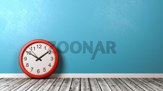 Red Clock on Wooden Floor Against Blue Wall with Copyspace 3D Illustration