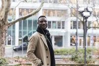 Fashionable Black Man Wearing Beige Coat Turning Towards Camera
