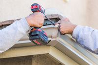 Workers Attaching Aluminum Rain Gutter to Fascia of House