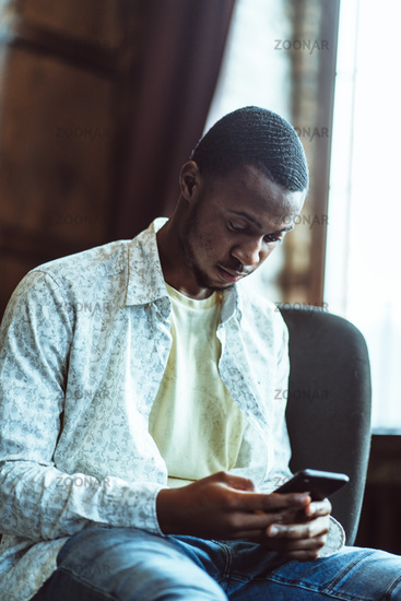 Young Black Guy Chats In Phone Sitting In Cozy Office