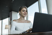 Young business woman using laptop computer in cafe or in coworking. Blond female working on laptop in an outdoor cafe.