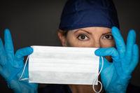 Female Doctor or Nurse Wearing Surgical Gloves Holding Up Medical Face Mask