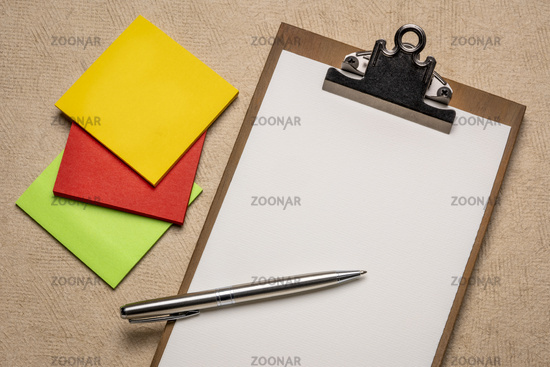 desktop concept - blank clipboard and sticky notes