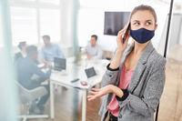 Business Frau mit Maske telefoniert mit Smartphone
