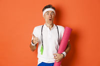 Concept of workout, gym and lifestyle. Close-up of happy and satisfied middle-aged athlete, showing thumb-up, like training session, holding yoga mat and skipping rope for fitness