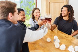 Glückliche Freunde zu Hause in WG beim Anstoßen mit Glas Rotwein