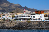 Tenerife, Spain - October 15, 2019: Waterside distant view Los Cristianos coastline, busy promenade waterfront street, touristic town, situated on south coast of Canary Islands, Spain