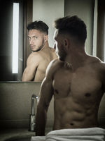 Shirtless handsome young man in bathroom by mirror