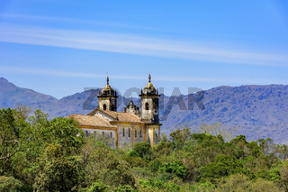 Rear view of historic church in baroque and colonial style from the 18th century amid the hills and vegetation