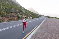 Fit african american woman in sportswear running on a coastal road