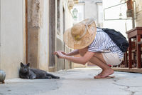 Female tourist woman wearing big straw hat on summer vacation in ald traditional Mediterranean town, squating on old stone pedestrian street and taking photo of lazy gray cat lying in front of house.