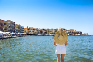 Young blond woman in big hat enjoying the beautiful views of the port of Chania
