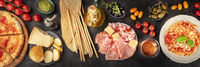 Italian food panorama. Pizza, pasta, cheese, ham, capers, wine, tomatoes, shot from the top on a black background