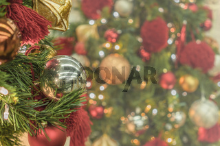 Blur bokeh background of Christmas tree ornament lights with glitter decoration balls in foreground.