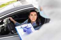 healthcare worker with clipboard and woman in car
