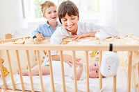 Mutter mit Kind streichelt Baby in Babybett