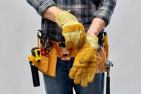 builder with working tools putting gloves on