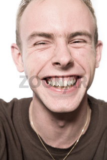 Studio portrait of a young man laughing loud