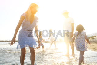 Happy family running in sea water