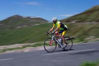 Ein Mitzieher eines Radrennfahrers im Gebirge in der Seitenansicht