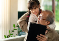 elderly man with granddaughter using tablet together