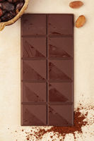 Chocolate bar background with cocoa powder and whole beans.