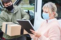 Paketdienst prüft Checkliste mit Paketboten und Paket