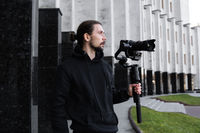 Young Professional videographer holding professional camera on 3-axis gimbal stabilizer. Pro equipment helps to make high quality video without shaking. Cameraman wearing black hoodie making a videos.