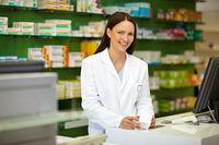 Apothekerin an Kasse mit Medikament