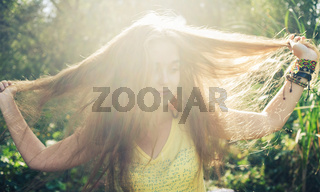 Portrait of happy woman with hand in hair against nature